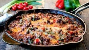 Poêle de fonte remplie de chili au boeuf gratiné avec poivrons et haricots verts
