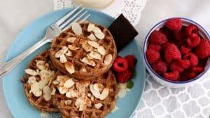 Assiette bleue contenant 3 gaufres sans gluten avec framboises et amandes effilées