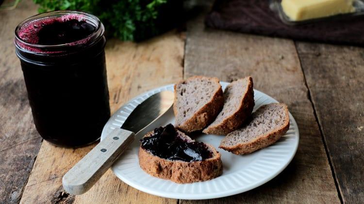 Pot de gelée de raisins avec quelques tranches de pain cétogène et de la gelée sur une d'entre elles