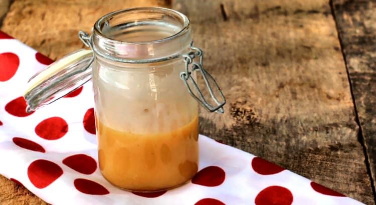 Sauce au caramel sans sucre dans un pot de verre sur napperon blanc à pois rouge