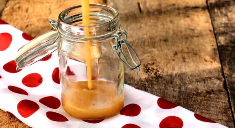 Sauce au caramel sans sucre déversée en filet dans un pot de verre sur napperon blanc à pois rouge