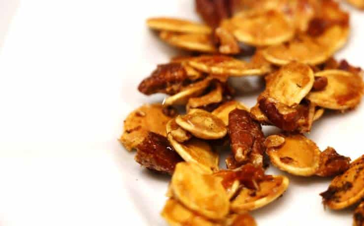 Vue de près des graines de citrouille au four à l'érable sur assiette blanche