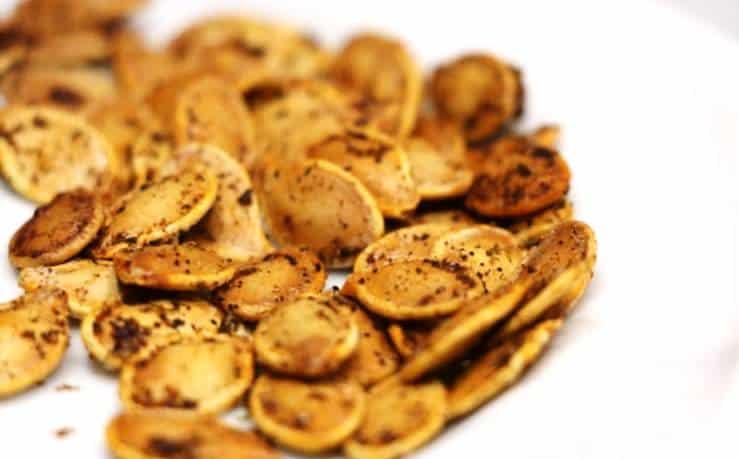 Sur une assiette blanche, des graines de citrouille grillées au four à la mexicaine