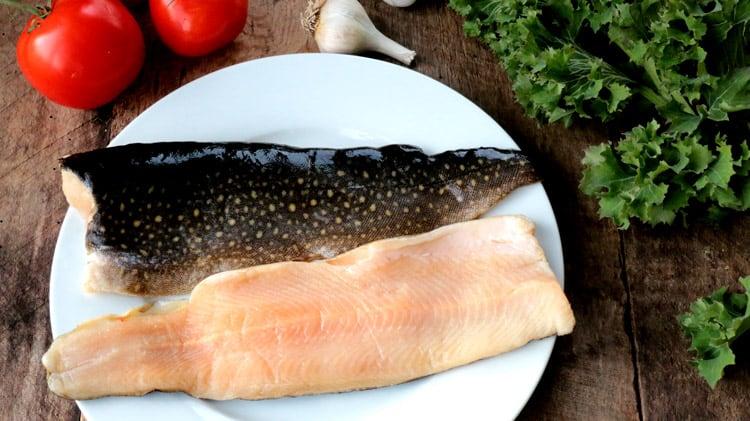 2 filets de truite grise crue sur assiette blanche et planche de bois avec tissu blanc à pois rouge