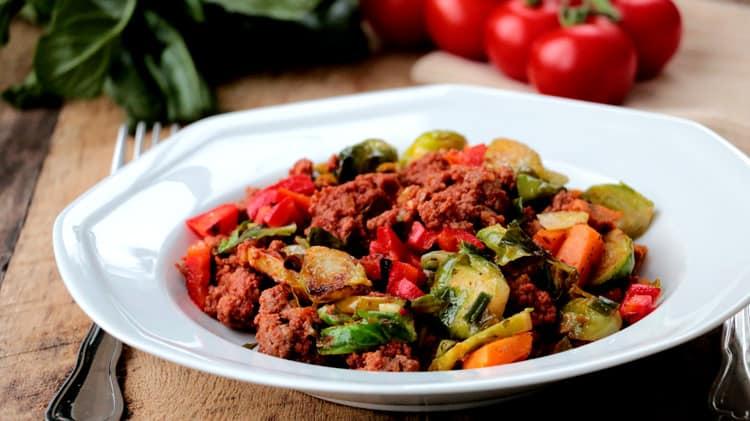 Assiette blanche de recette de boeuf haché aux légumes sur planche de bois avec tomates et verdure en arrière-plan