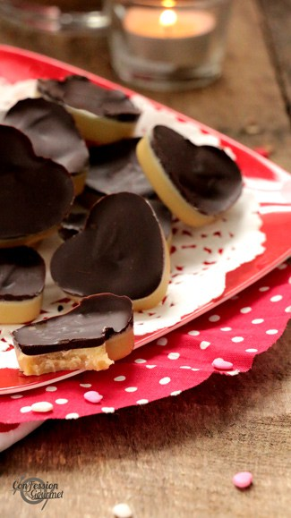 Image verticale des bouchées au chocolat avec chandelle en arrière-plan et petits coeurs bonbons sur planche de bois