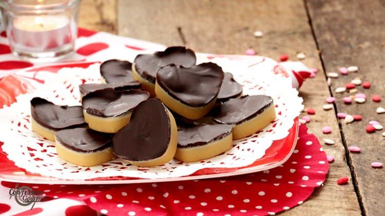 Un paquet de petits coeurs de bouchées au chocolat sur assiette rouge, linge blanc à pois rouge et petits bonbons en coeur sur planche de bois