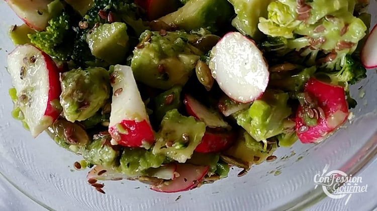 Sauce à l'avocat dans une salade de radis, concombres, brocoli avec graines de lin et de citrouille