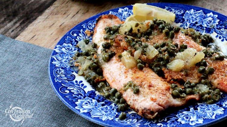 La truite à la poêle dans une assiette bleu royal sur planche de bois et tissu de napperon gris