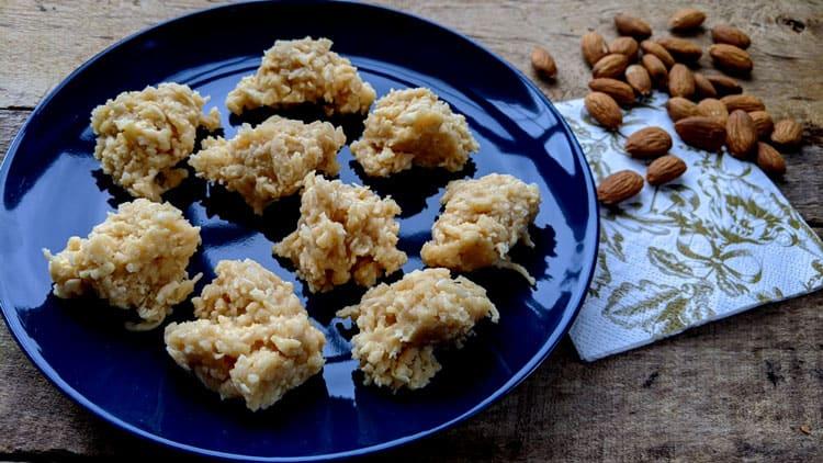 Bouchées noix de coco et caramel sur assiette bleu royal sur planche de bois et amandes