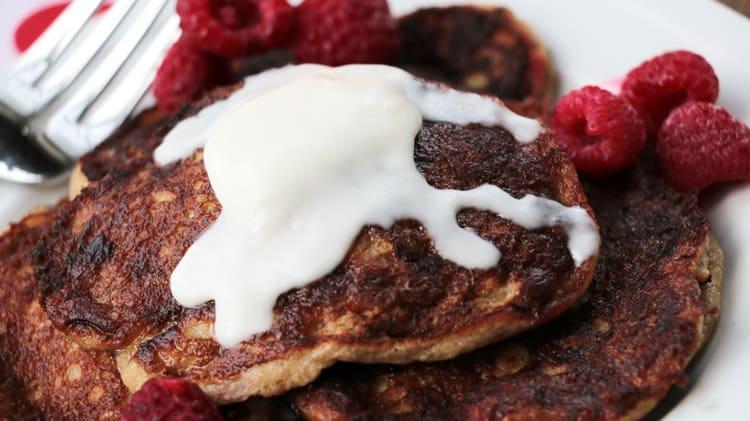 Vue de près des pancakes sans levure dans une assiette blanche avec framboises