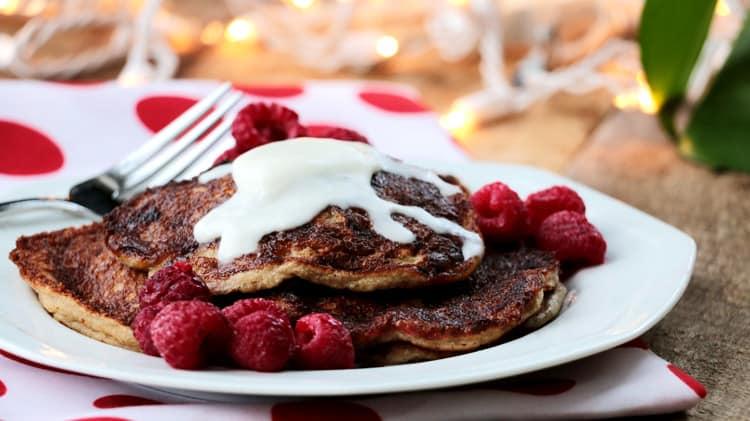 Assiette de pancakes sans levure avec framboises et coulis de beurre de coco sur tissu blanc à gros pois rouge
