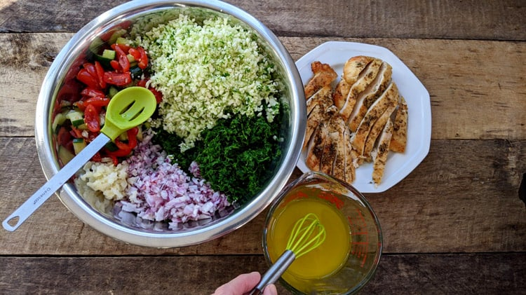 Bol contenant tous les ingrédients du taboulé de chou-fleur, assiette avec poulet et tasse contenant la vinaigrette avec fouet