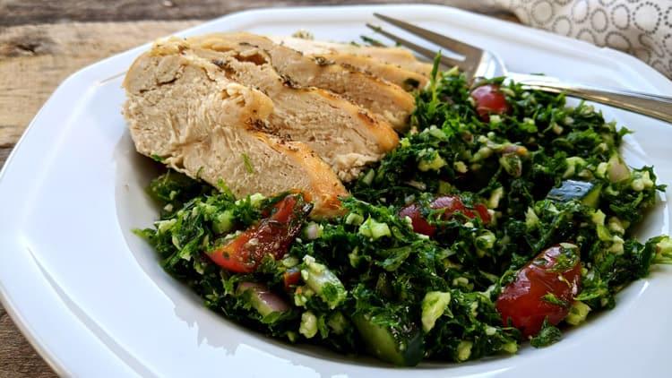 Assiette blanche avec du taboulé de chou-fleur et quelques tranches de poulet sur planche de bois