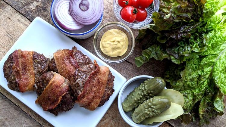 Hamburgers au four sur assiette blanche avec Dijon, laitue, oignon rouge et cornichons sur planche de bois