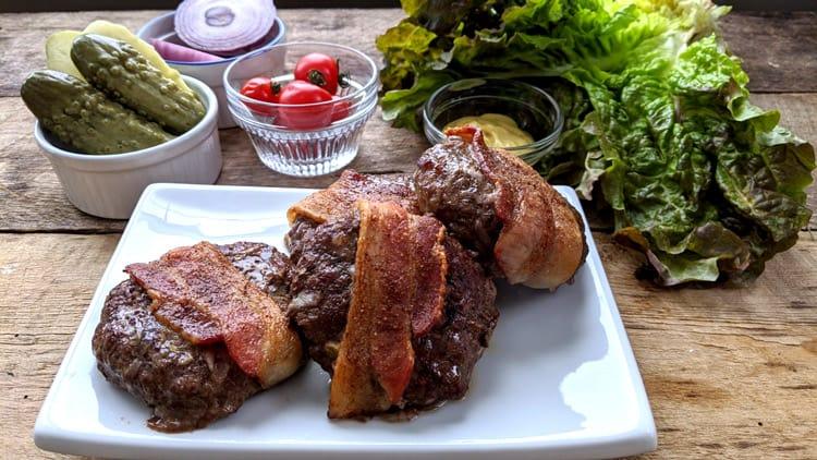 Vue de près des hamburgers au four avec bacon sur assiette blanche et garnitures en arrière-plan