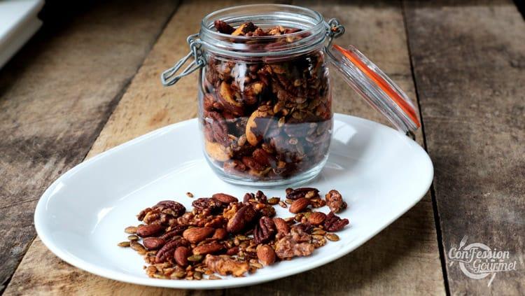 Pot de verre contenant le mélange de noix épicées sur assiette blanche et planche de bois