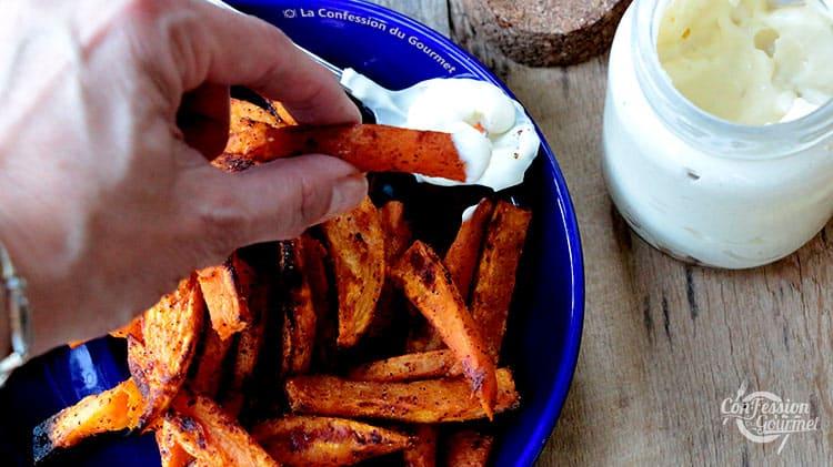 Une main tenant une des frites de patates douces au four avec un peu de mayonnaise maison