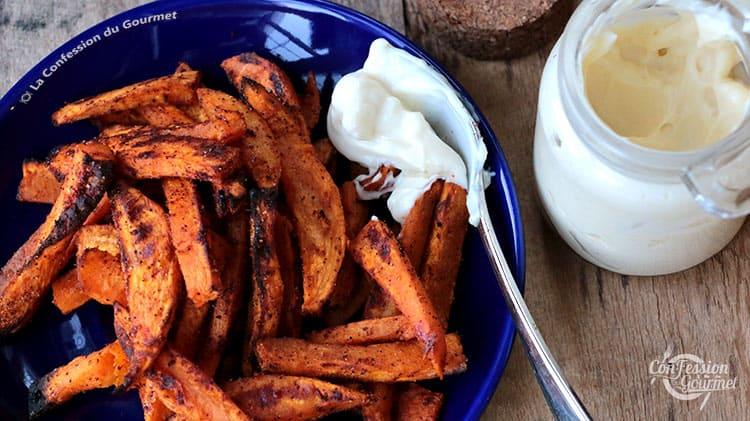 Assiette bleue contenant les frites de patates douces au four avec une cuillère remplie de mayonnaise
