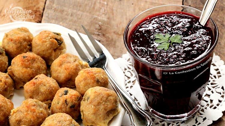 Boulettes de dinde sur assiette vue de près avec un pot de sauce framboise sur napperon dentelle en papier