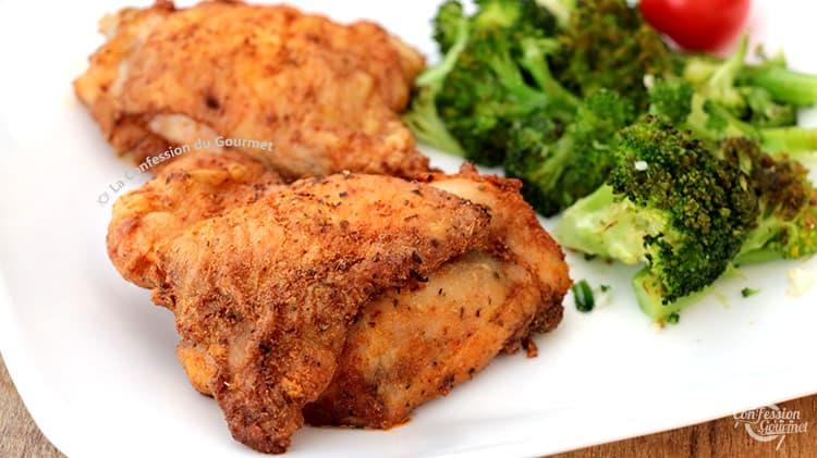 Deux hauts de cuisse de poulet croustillant au four avec brocoli en arrière plan sur assiette blanche