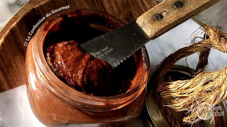 Pot de beurre de noisettes maison avec couteau à tartiner dans le pot