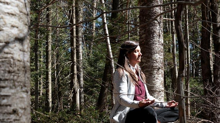 Johanne en méditation dans la forêt au soleil après avoir cuisiné sa sauce bbq maison