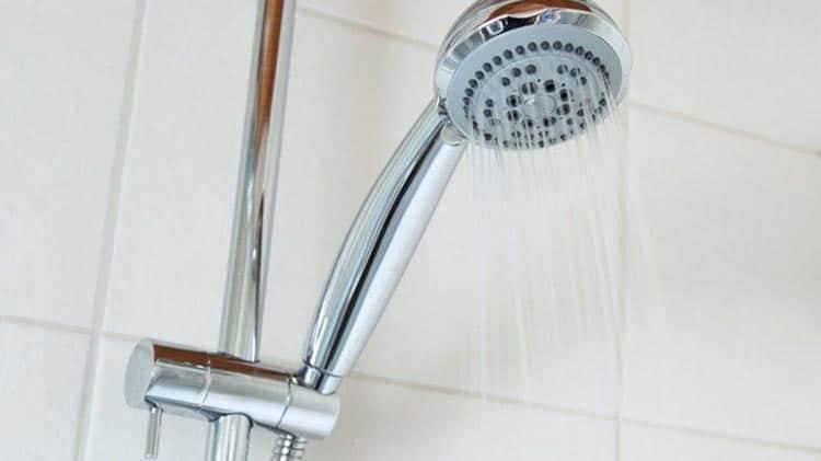 Robinet de douche qui coule et céramique blanche