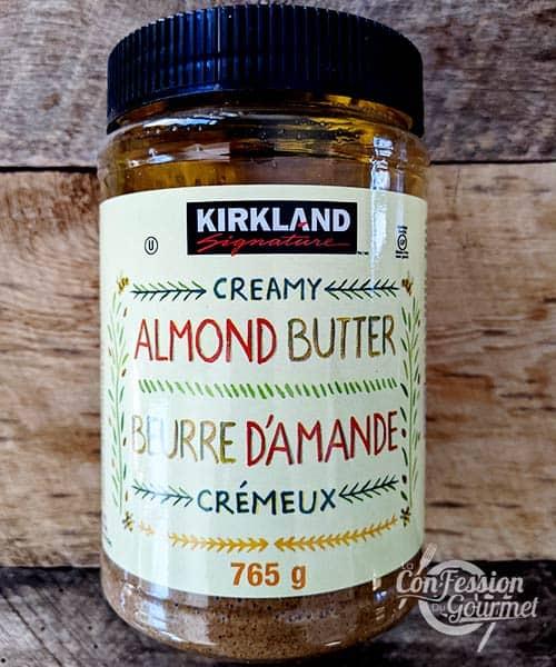 Pot de beurre d'amandes sur planche de bois