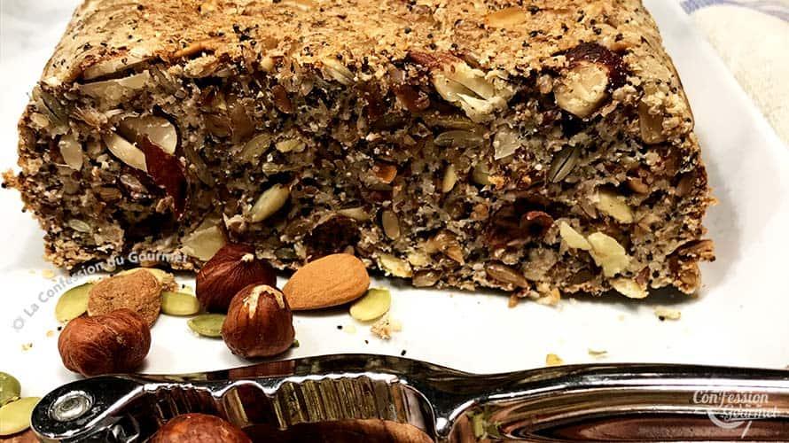 Vue de près du pain aux graines tranché avec casse noix et quelques noisettes