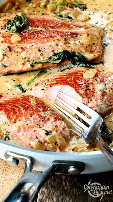 Vue à angle du saumon à la Toscane dans la poêle blanche et fourchette