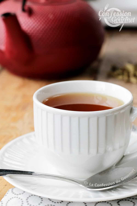 Thé menthe poivrée chocolat dans une tasse blanche avec théière en fonte en arrière-plan