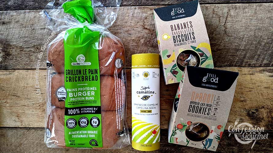 Pains burgers au grillon, tube de graines de caméline et biscuits Still Good sur planche de bois