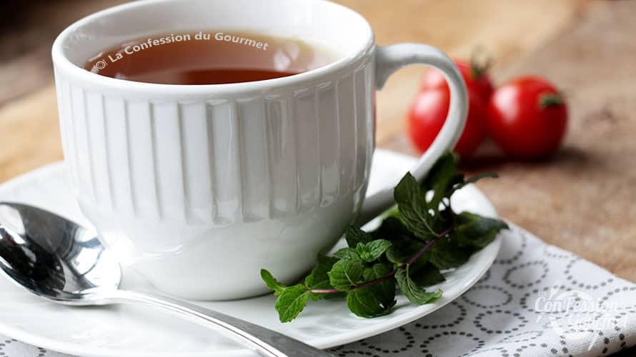 Tasse blanche avec le thé menthe poivrée et chocolat sur planche de bois