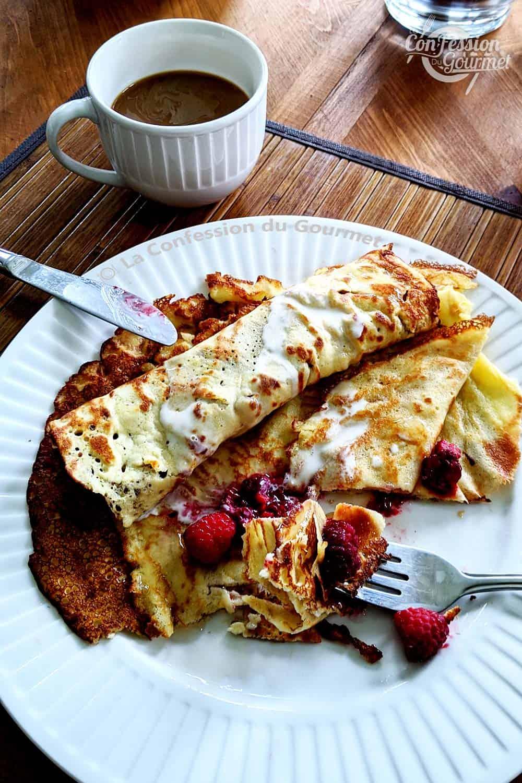 Fourchette avec bouchée de crêpes au lait d'amandes au dessus de l'assiette servie