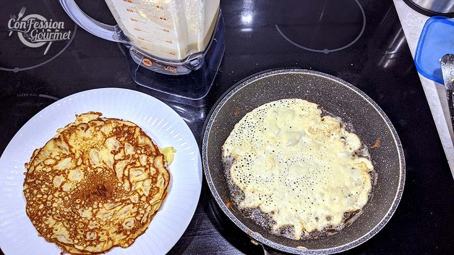 Crêpe cuisant dans la poêle et assiette blanche contenant une crêpe déjà cuite